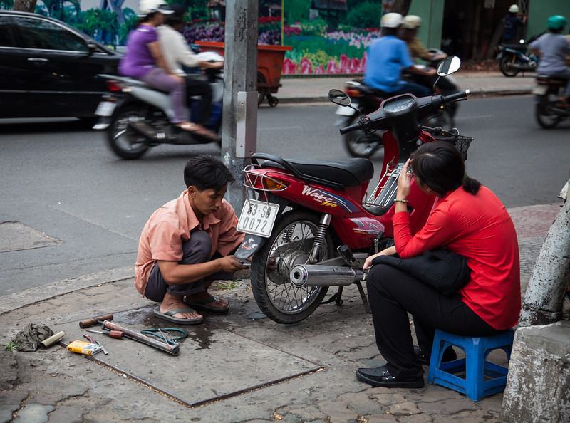 "A woman stops at a roadside ""shop"" to have a flat tire on her motorcycle repaired."