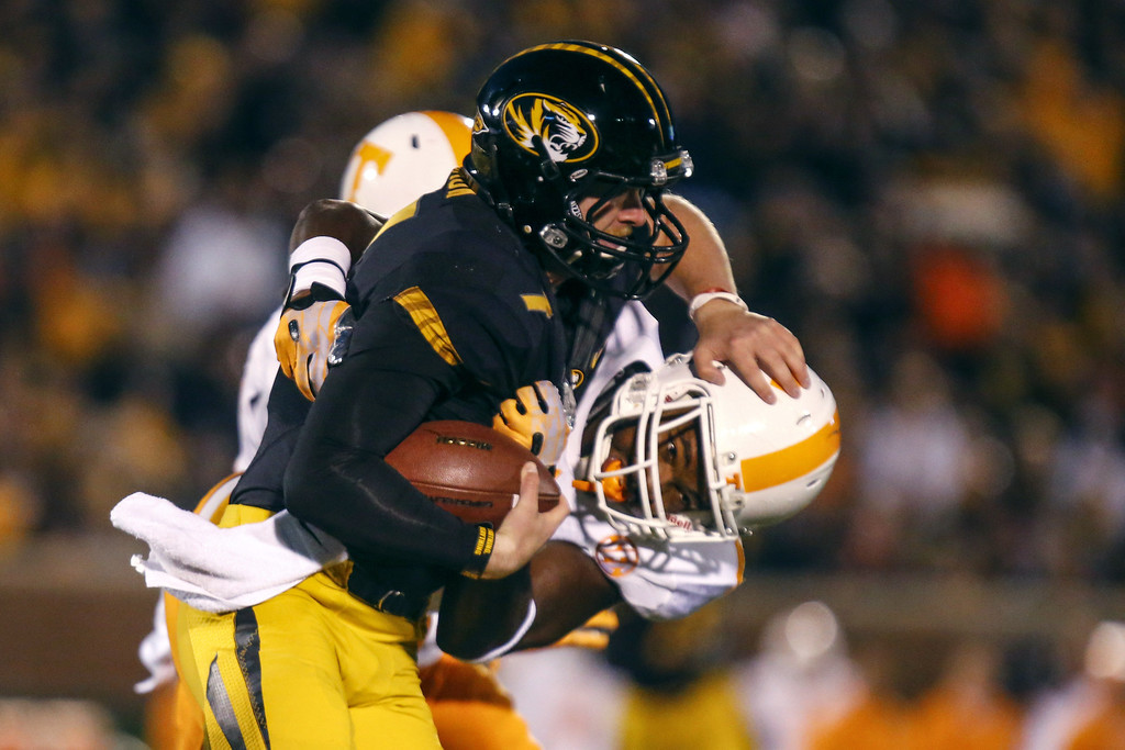 . Maty Mauk #7 of the Missouri Tigers attempts to break away from Dontavis Sapp #41 of the Tennessee Volunteers in the first quarter on November 2, 2013 at Faurot Field/Memorial Stadium in Columbia, Missouri. (Photo by Kyle Rivas/Getty Images)
