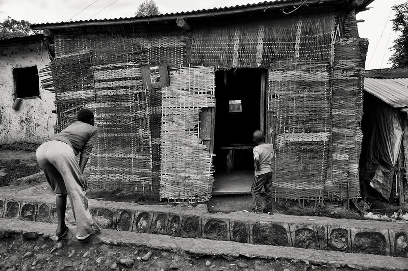 Few families own a television set in the town of Jinka. So many people pay to go into one of these TV huts to view there favourite program, or like these two kids they just try and get a peep from outside.  Jinka, Southern Ethiopia, 2013.