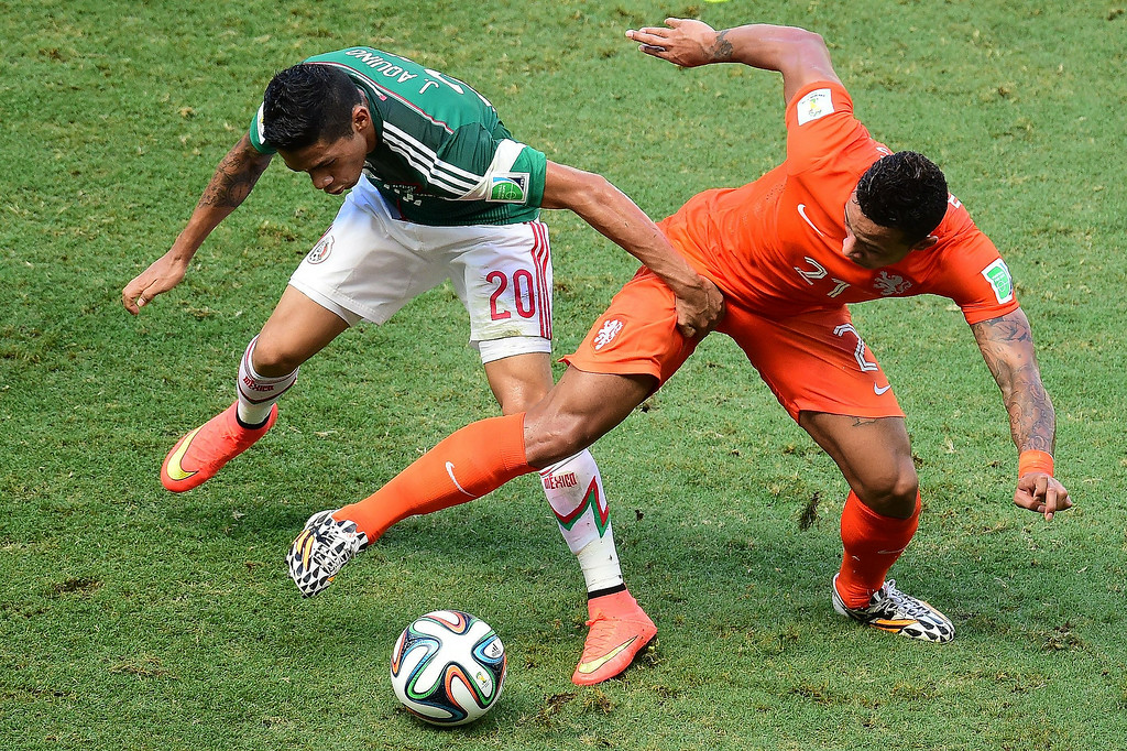 . Netherlands\' forward Memphis Depay (R) and Mexico\'s midfielder Javier Aquino vie for the ball during a Round of 16 football match between Netherlands and Mexico at Castelao Stadium in Fortaleza during the 2014 FIFA World Cup on June 29, 2014.   JAVIER SORIANO/AFP/Getty Images