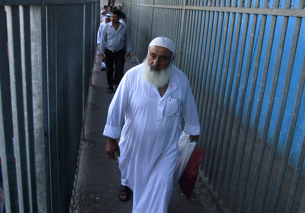 . Palestinian Muslim worshipers walk through Israel\'s controversial separation barrier on the outskirts of the West Bank town of Bethlehem as they undergo security checks by Israeli security forces before heading to Jerusalem to attend  Friday prayers at the Al-Aqsa mosque compound on July 26, 2013 during the Muslim fasting month of Ramadan.   MUSA AL-SHAER/AFP/Getty Images