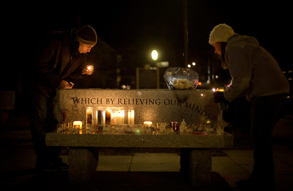 . Brian Tenenhaus, left, blows out a match after lighting a candle at a vigil outside the Edmond Town Hall with Lauren Foster, right, Saturday, Dec. 15, 2012, in Newtown, Conn. A gunman walked into Sandy Hook Elementary School in Newtown Friday and opened fire, killing 26 people, including 20 children. (AP Photo/David Goldman)