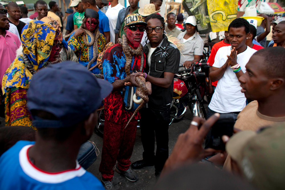 . In this Jan. 27, 2013 photo, snake handler Saintilus Resilus, center left, holds his snake as he poses for photos with a spectator as he performs for money during pre-Lenten Carnival season in Petionville, Haiti. Resilus has used snakes and other animals to earn a little money since at least 1974. (AP Photo/Dieu Nalio Chery)