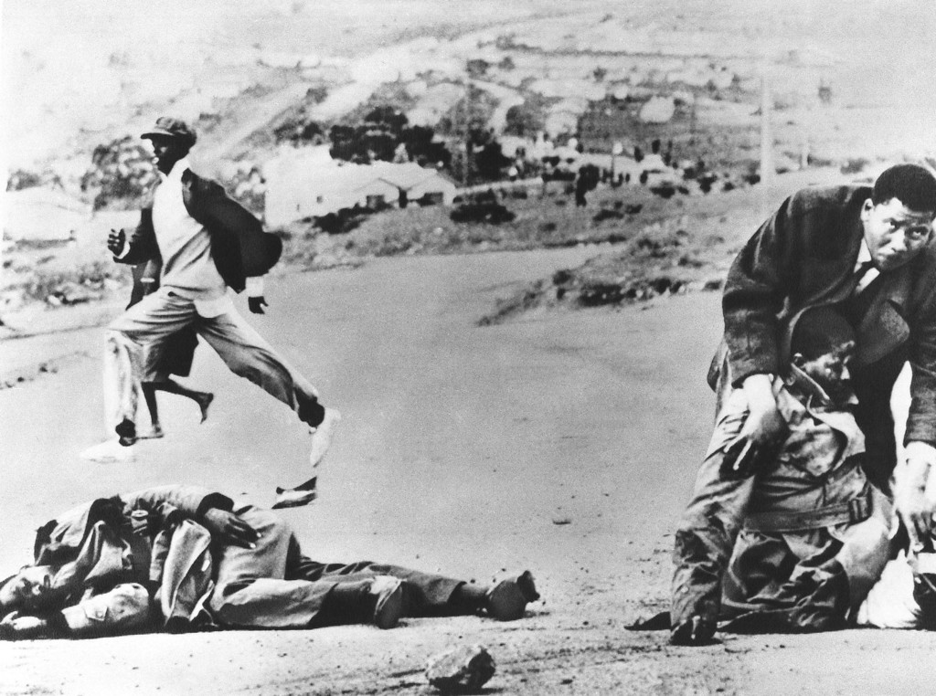 . One black South African policeman lies dead on the ground, left, while another is aided by an unidentified man at right, after the two constables were stoned by an angry crowd at East London, South Africa on Sunday, Sept. 26, 1977. The second policeman died later in a hospital. The bloodshed followed an emotional funeral for black leader Steve Biko. (AP Photo)