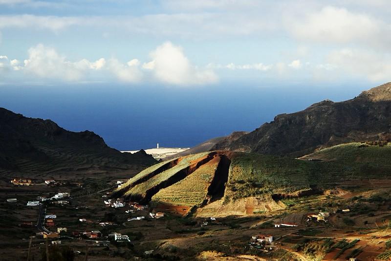 Pozoruhodná hora u vesnice El Palmar. V pozadí maják u Buenavista el Norte.