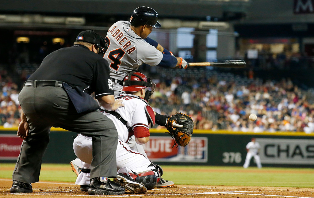 . Detroit Tigers\' Miguel Cabrera, top, connects on a run-scoring single as Arizona Diamondbacks\' Miguel Montero, bottom right, and umpire Fieldin Culbreth, left, look on during the first inning of a baseball game on Tuesday, July 22, 2014, in Phoenix. (AP Photo)