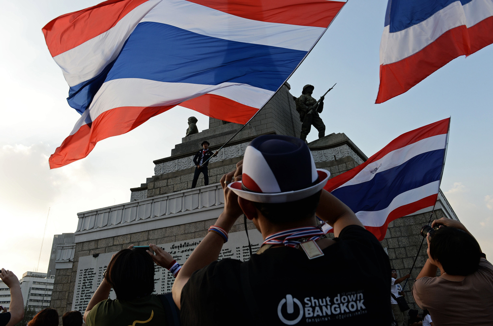 """. Thai anti-government protesters take pictures as a man waves a giant national flag from the Victory Monument, one of the sites occupied by protesters in Bangkok on January 13, 2014.  Tens of thousands of Thai opposition protesters occupied major streets in central Bangkok on January 13 in an attempted \""""shutdown\"""" of the capital, escalating a campaign to unseat the embattled premier.    (CHRISTOPHE ARCHAMBAULT/AFP/Getty Images)"""