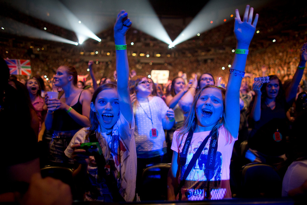 . British boy-band One Direction fans in the front row react to the band early in their show Thursday night, July 18, 2013 at the Target Center in Minneapolis.  (AP Photo/Star Tribune, Jeff Wheeler)