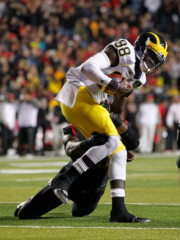 . Rutgers\' Darius Hamilton tackles Michigan quarterback Devin Gardner (98) on the 4-yard line during the first half of an NCAA college football game Saturday, Oct. 4, 2014, in Piscataway, N.J. (AP Photo/Rich Schultz)