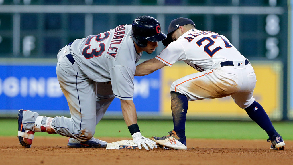 . Cleveland Indians left fielder Michael Brantley (23) is safe at second on his double as Houston Astros second baseman Jose Altuve (27) tries to tag during the ninth inning of a baseball game, Sunday, May 20, 2018, in Houston. (AP Photo/Michael Wyke)