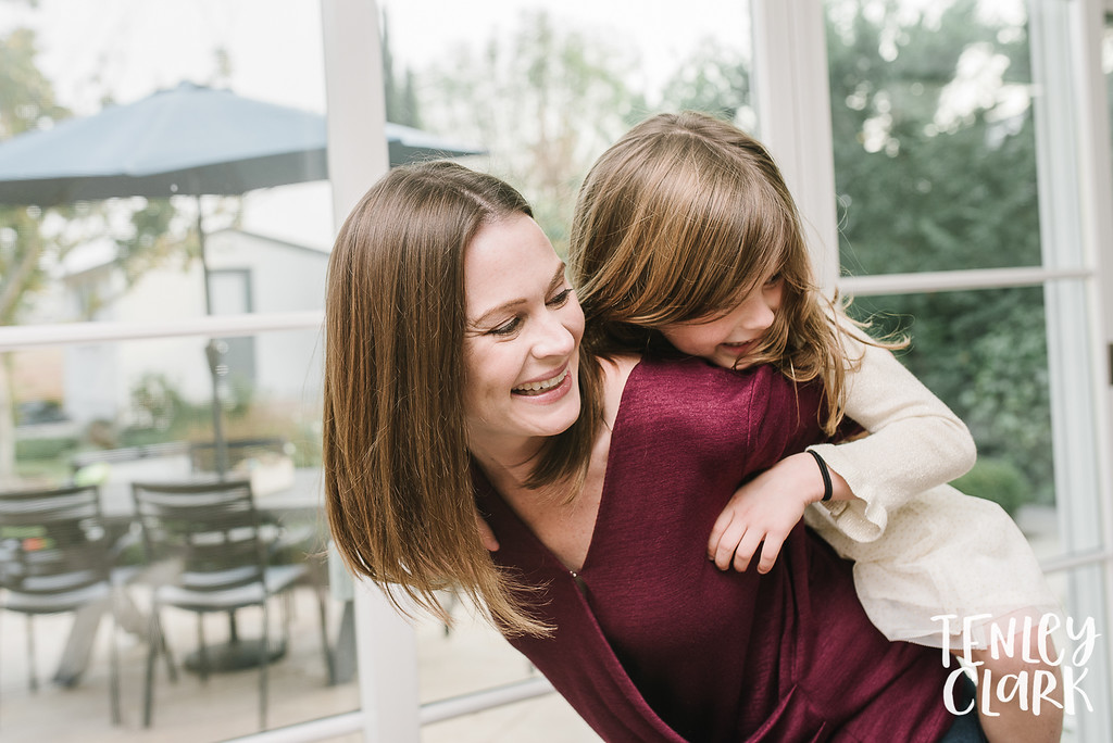 Daughter on mom's back. Lifestyle in-home family photoshoot in Marin, CA by Tenley Clark Photography.
