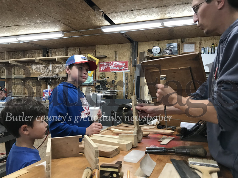 Aiden, 13, and Jase, 7, Powell of Penn Hills watch as Mike Standish, a Northwest Pennsylvania Steam Engine and Old Equipment Association Inc. member, explains 19th century woodworking. Photo by Gabriella Canales