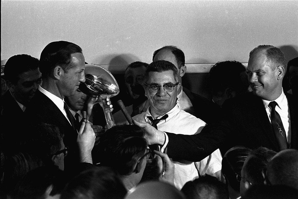 Description of . Football commissioner Pete Rozelle, left, presents the trophy to Coach Vince Lombardi of the Green Bay Packers in Los Angeles January 15, 1967, after the Packers trounced the Kansas City Chiefs 35 to 21 in the first Super Bowl football game. (AP Photo)