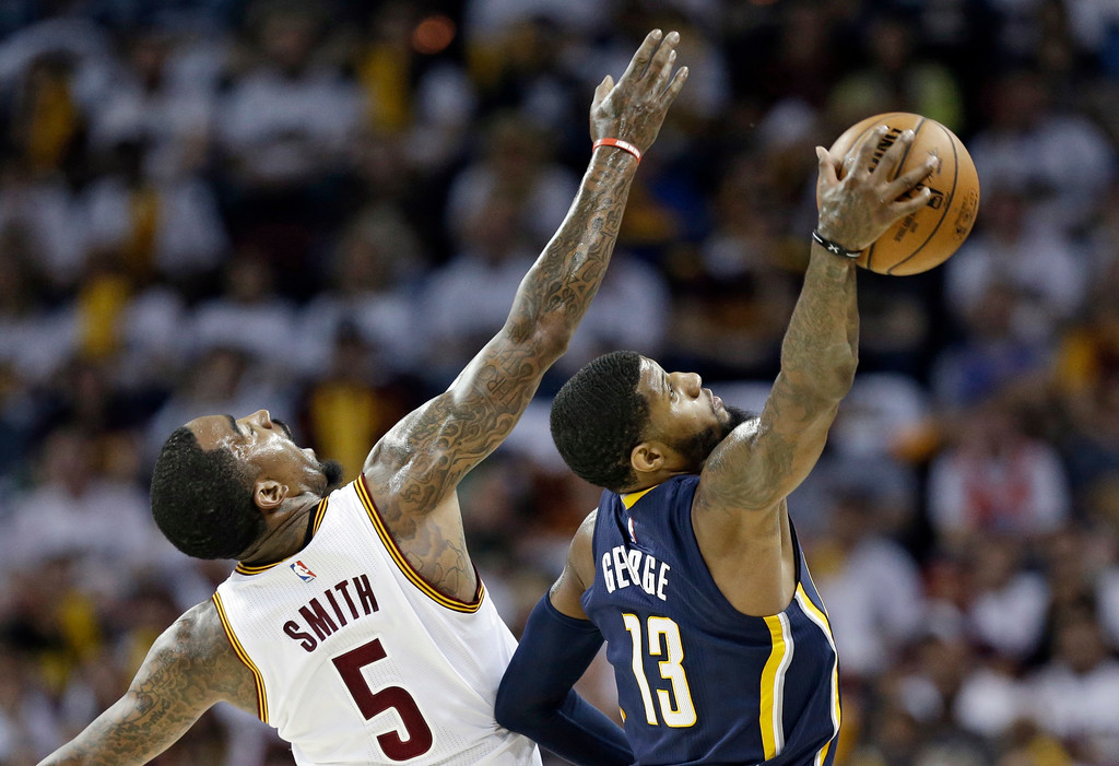. Indiana Pacers\' Paul George (13) grabs a pass ahead of Cleveland Cavaliers\' J.R. Smith (5) in the first half in Game 1 of a first-round NBA basketball playoff series, Saturday, April 15, 2017, in Cleveland. (AP Photo/Tony Dejak)