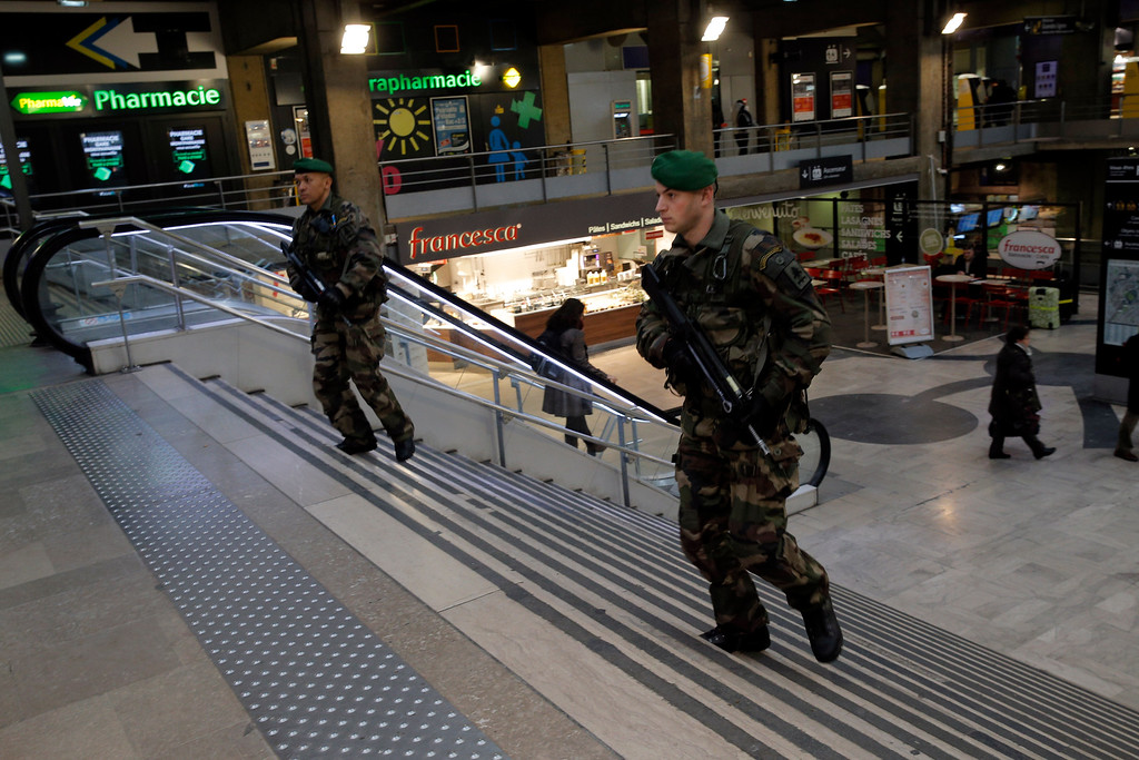 . French soldiers patrol at the Montparnasse railway station in Paris, France, Wednesday, Jan. 7, 2015.  France reinforced security at houses of worship, stores, media offices and transportation after masked gunmen stormed the offices of a French satirical newspaper Wednesday, killing at least 12 people before escaping, police and a witness said.  (AP Photo/Christophe Ena)
