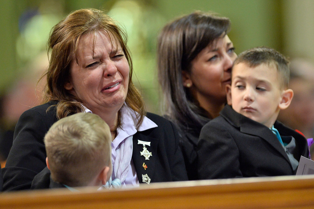 . Kathy Cirillo cries during the regimental funeral service for her son, Cpl. Nathan Cirillo, as Marcus Cirillo, Nathan Cirillo\'s son his held by his aunt Natasha Cirillo in Hamilton, Ontario  on Tuesday, Oct. 28, 2014.    (AP Photo/The Canadian Press, Nathan Denette)