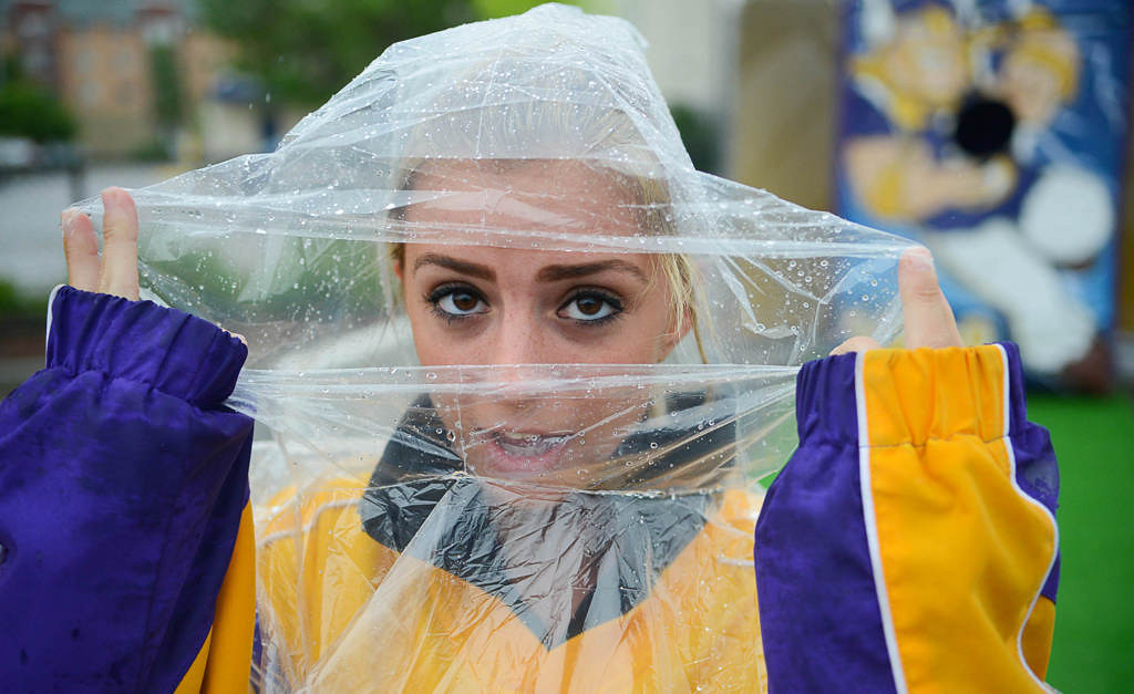. University of Minnesota  student Jasmine Auger, 22, tries to stay dry as she waits for someone to play a game set up at the Stadium Village stop on opening day. (Pioneer Press: Ben Garvin)