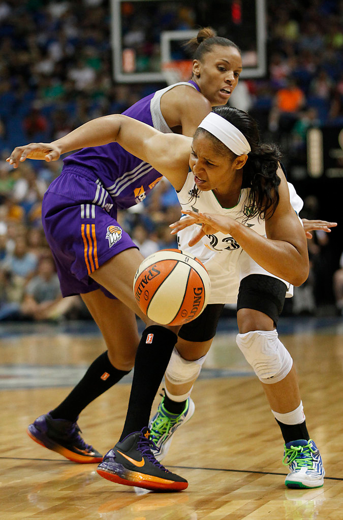 . Minnesota Lynx forward Maya Moore, right,  pushes the ball around the defense of Phoenix Mercury guard DeWanna Bonner, left, in the first half. (AP Photo/Stacy Bengs)