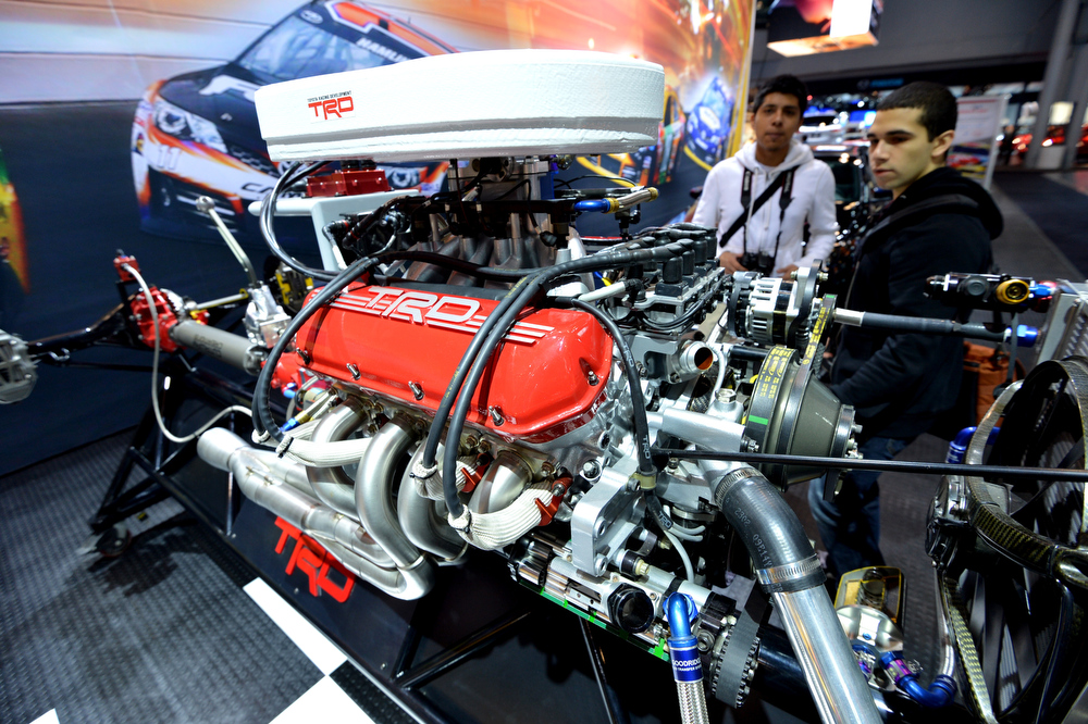 Description of . Two men look at a Toyota Racing Development engine built for their Nascar race car at a public preview of the New York International Auto Show on March 29, 2013 in New York.  STAN HONDA/AFP/Getty Images