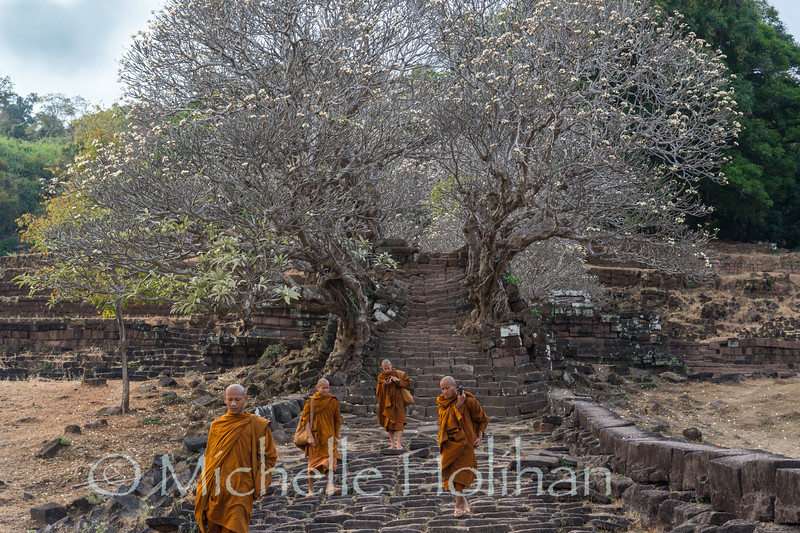 CHAMPASAK, LAOS - JANUARY 19, 2019: Unidentified Buddhist monks walk down a staircase at the Wat Phu Temple World Heritage Site.