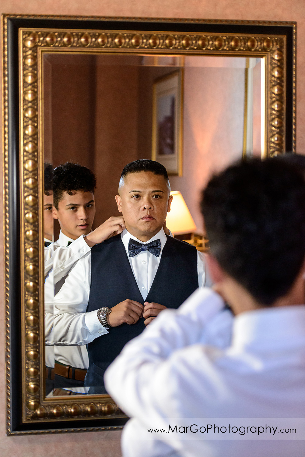 groom getting ready in front of the mirror at Whitcomb Hotel in San Francisco