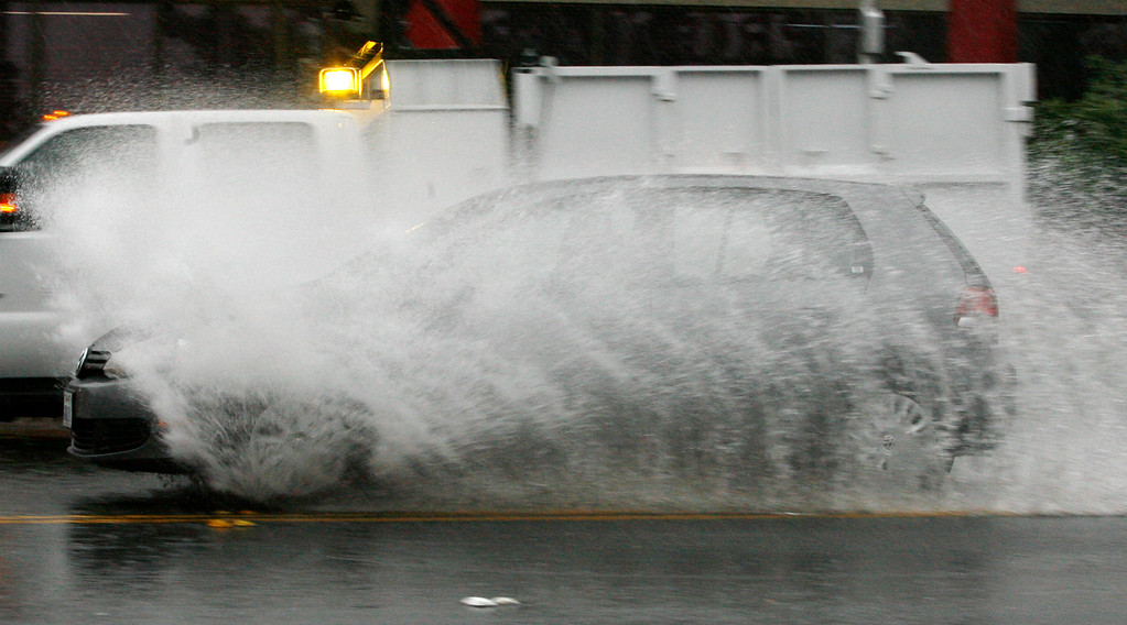 . A car drives through flood waters at Coleman Avenue and Emory Street in San Jose, Calif., on Thursday, Dec. 11, 2014. (Gary Reyes/Bay Area News Group)