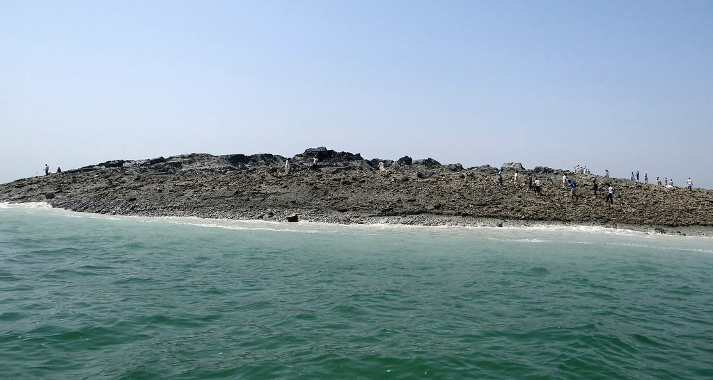 . In this photo released by the Gwadar local government office on Wednesday, Sept 25, 2013, people walk on an island that reportedly emerged off the Gwadar coastline in the Arabian Sea. A deadly magnitude 7.7 earthquake struck in the remote district of Awaran in Pakistan\'s Baluchistan province with enough force to create a small island visible off the southern coast, Pakistani officials said. (AP Photo/Gwadar local government office)