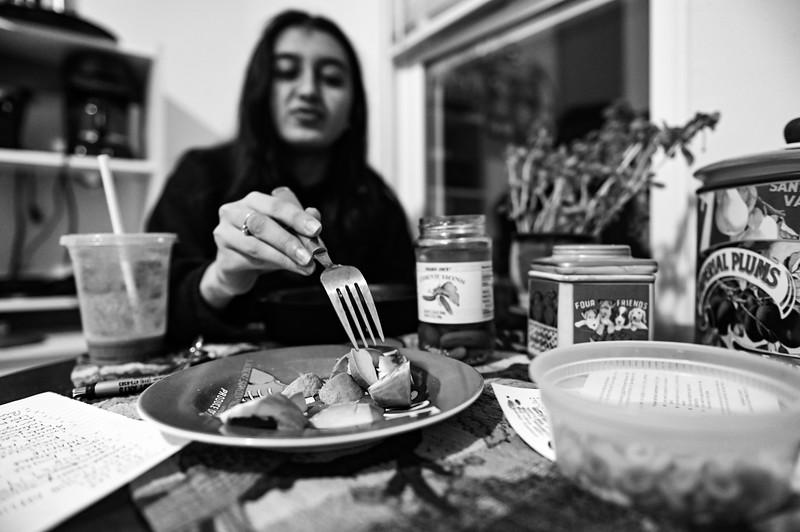 Aanya eats dinner by herself before her group meeting.