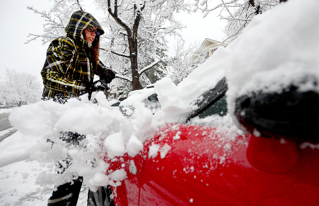 . Gabriella Garcia brushes snow off of her car near 10th and Euclid at another spring snow storm hits in Boulder, Colorado May 1, 2013.  DAILY CAMERA/ MARK LEFFINGWELL