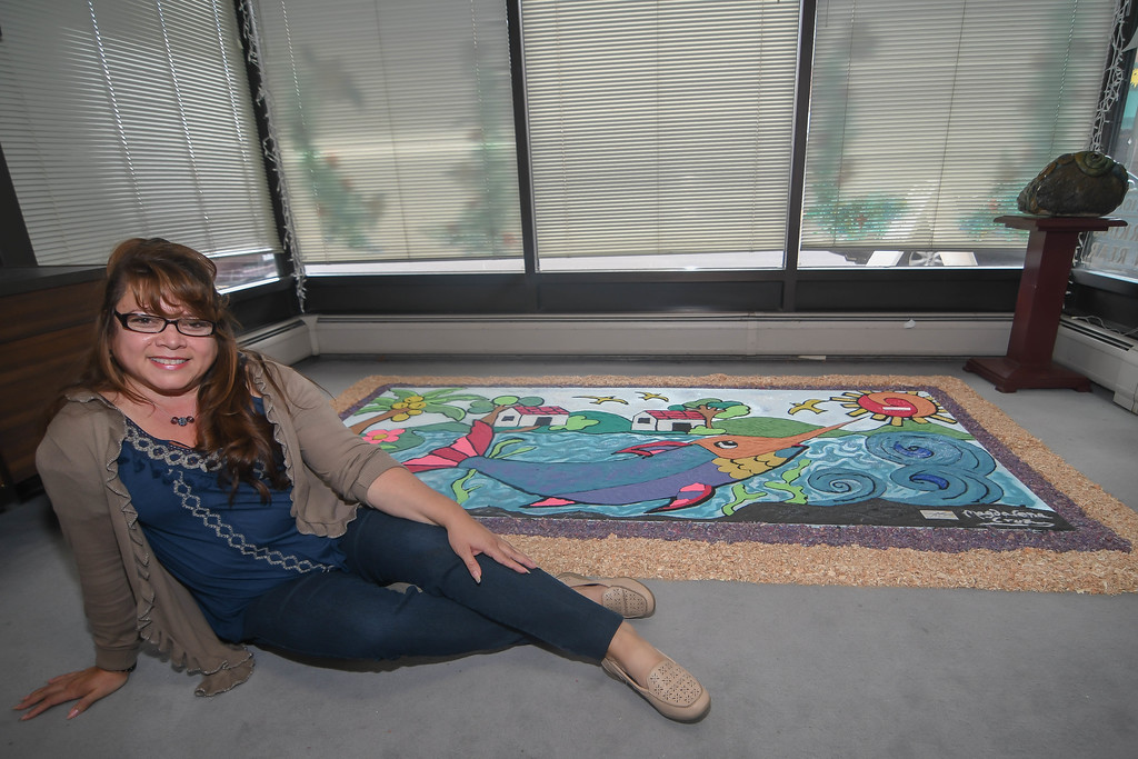 . Eric Bonzar � The Morning Journal <br> María Magdalena Cruz, of Lorain, sits alongside her sand art which will be featured inside of the Lorain Arts Council, 737 Broadway, during FireFish Festival on Oct. 6-7. The 48-year-old, Salvadoran native also will showcase her talents live as she will create a second piece in front of 657 Broadway at 3 p.m., Oct. 7.