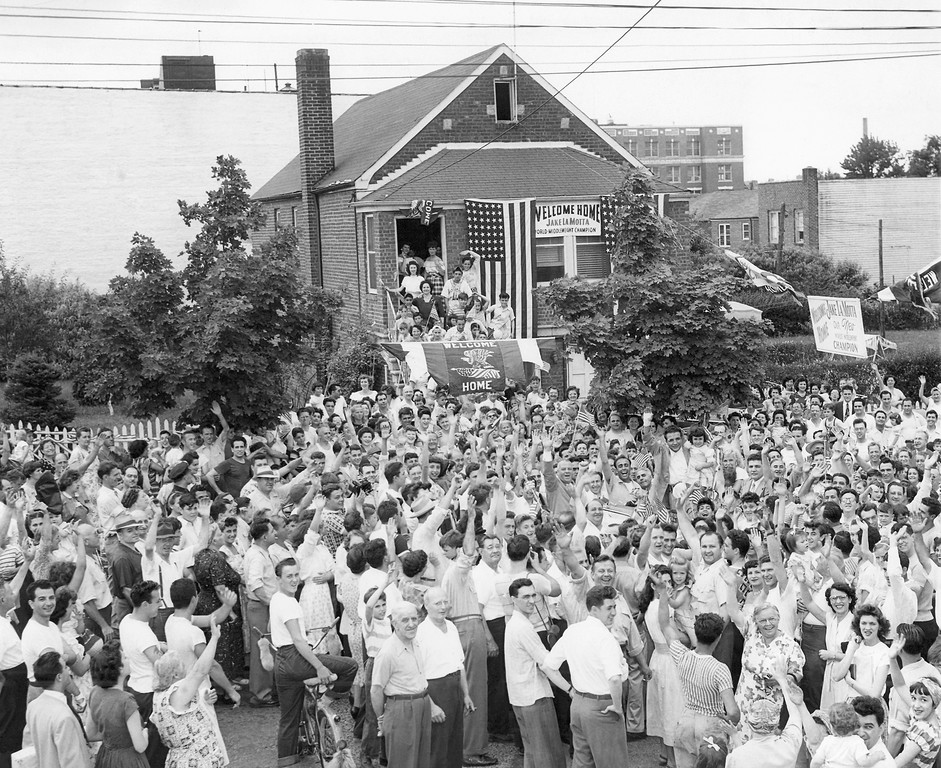 . In this June 18, 1949, file photo, a crowd gathers in front of Jake Lamotta\'s home in the Bronx borough of New York, welcoming him home from Detroit, Mich., where he won the middleweight boxing championship against Marcel Cerdan. LaMotta, whose life was depicted in the film �Raging Bull,� died Tuesday, Sept. 19, 2017, at a Miami-area hospital from complications of pneumonia. He was 95. (AP Photo/File)