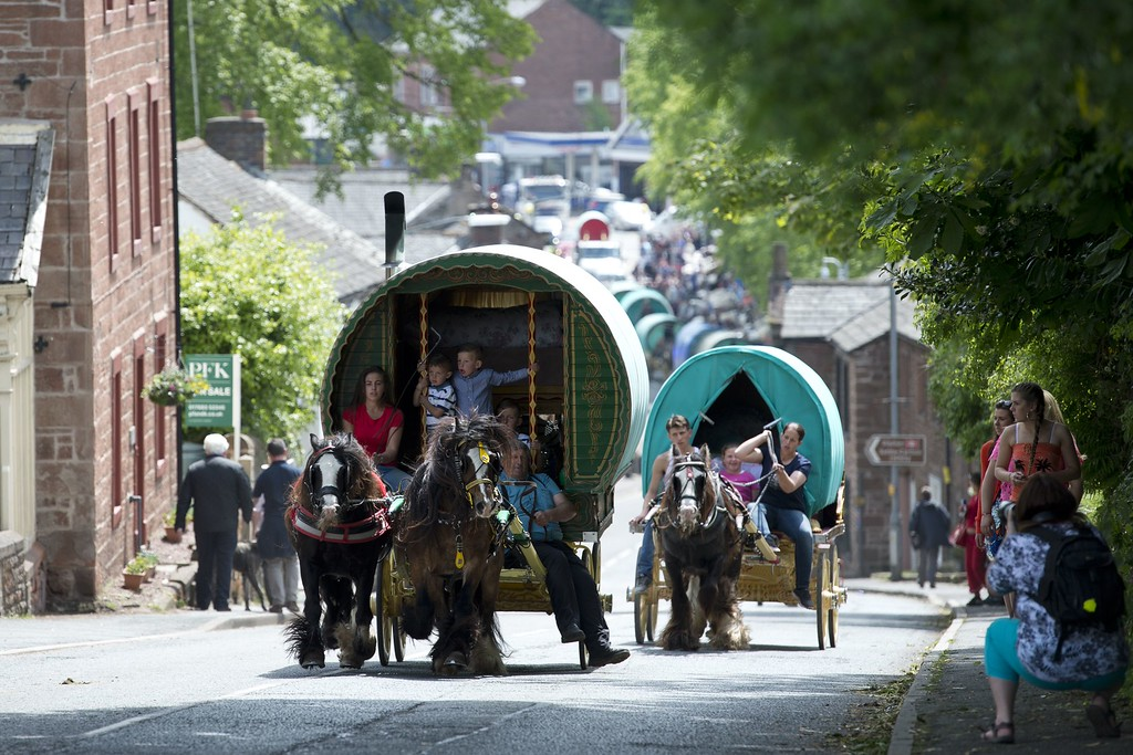. People ride their vardos, or horse-drawn caravans, along a road on the opening day of the annual Appleby Horse Fair, in the town of Appleby-in-Westmorland, North West England on June 4, 2015. The annual event attracts thousands of travelers from across Britain to gather and buy and sell horses. AFP PHOTO / OLI SCARFF/AFP/Getty Images