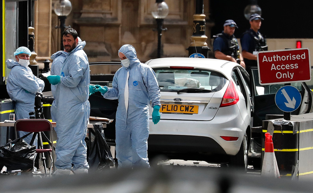 . Forensics officers work near the car that crashed into security barriers outside the Houses of Parliament in London, Tuesday, Aug. 14, 2018. Authorities said in a statement Tuesday that a man in his 20s was arrested on suspicion of terrorist offenses after a silver Ford Fiesta collided with a number of cyclists and pedestrians before crashing into the barriers during the morning rush hour. (AP Photo/Frank Augstein)