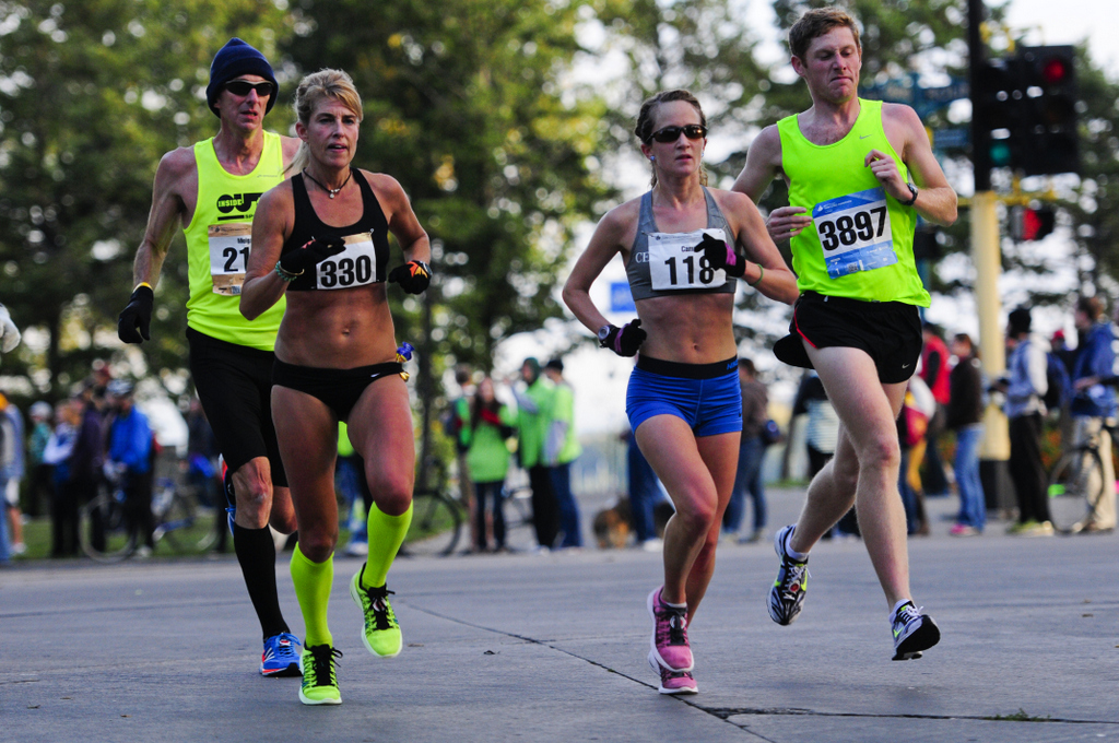 . Runners (foreground from left) Mandy Hall of Broken Arrow, Minn.; Kelly McDaniel of Rosemount; and Jacob Goertz traverse the marathon course near Lake Calhoun in Minneapolis. (Pioneer Press: Simon Guerra)