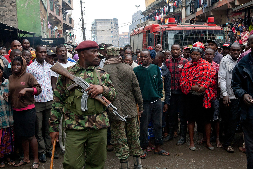 . A Kenyan Paramilitary soldier controls the crowd at the site of a building collapse in Nairobi, Kenya, Saturday, April 30, 2016. (AP Photo/Sayyid Abdul Azim)