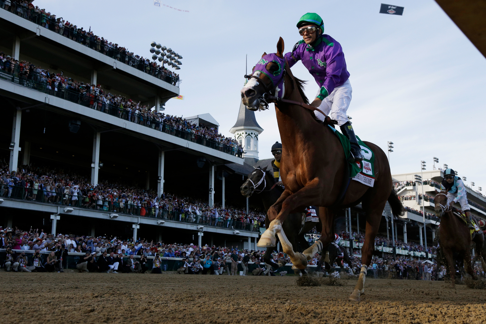 Description of . Victor Espinoza rides California Chrome to victory during the 140th running of the Kentucky Derby horse race at Churchill Downs Saturday, May 3, 2014, in Louisville, Ky. (AP Photo/David J. Phillip)