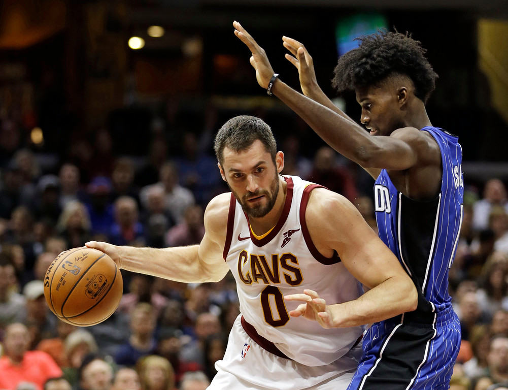 . Cleveland Cavaliers\' Kevin Love, left, drives past Orlando Magic\'s Jonathan Isaac in the first half of an NBA basketball game, Saturday, Oct. 21, 2017, in Cleveland. (AP Photo/Tony Dejak)
