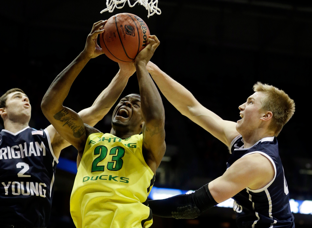 . Oregon forward Elgin Cook (23) battle for a rebound against BYU guard Matt Carlino (2) and forward Eric Mika during the second half of a second-round game in the NCAA college basketball tournament Thursday, March 20, 2014, in Milwaukee. (AP Photo/Morry Gash)