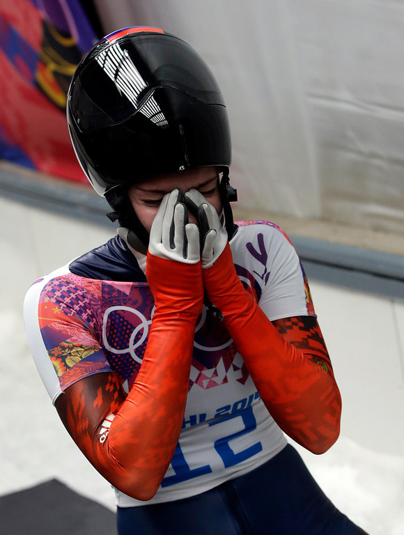 . Elena Nikitina of Russia reacts in the finish area after her final run during the women\'s skeleton competition at the 2014 Winter Olympics, Friday, Feb. 14, 2014, in Krasnaya Polyana, Russia. Nikitina won the bronze medal. (AP Photo/Dita Alangkara)