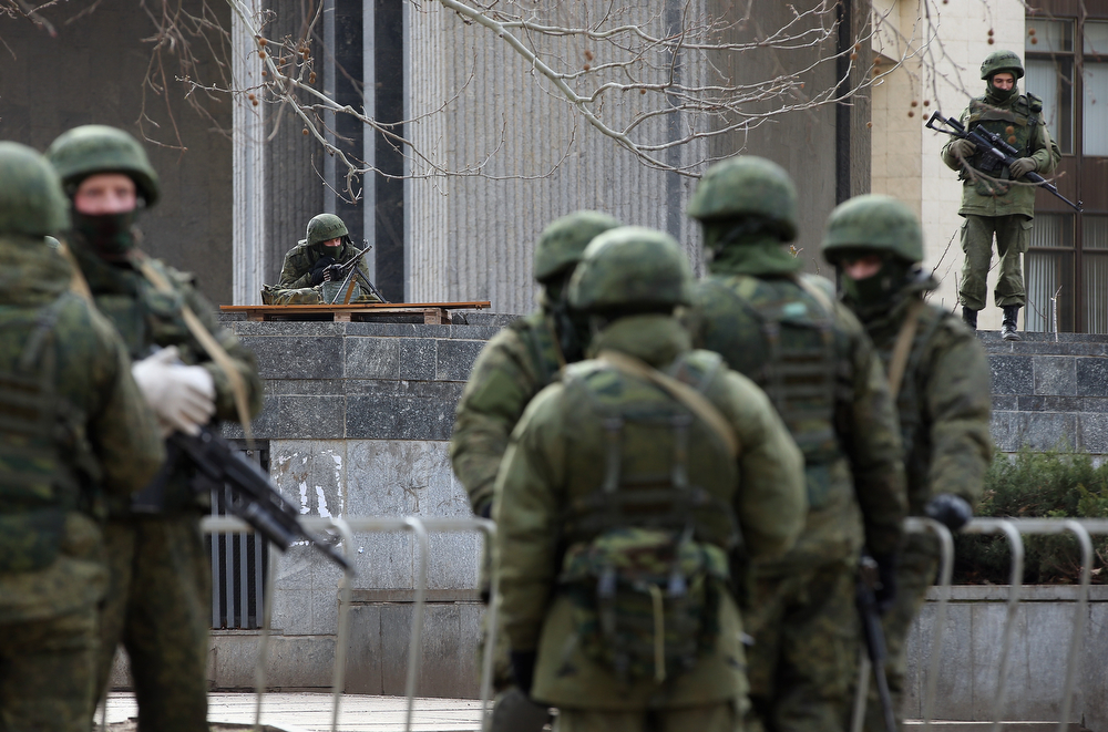 . Heavily-armed soldiers without identifying insignia guard the Crimean parliament building shortly after taking up positions there on March 1, 2014 in Simferopol, Ukraine. The soldiers\' arrival comes the day after soldiers in similar uniforms stationed themselves at Simferopol International Airport and Russian soldiers occupied the airport at nearby Sevastapol in moves that are raising tensions between Russia and the new Kiev government. Crimea has a majority Russian population and armed, pro-Russian groups have occupied government buildings in Simferopol.  (Photo by Sean Gallup/Getty Images)