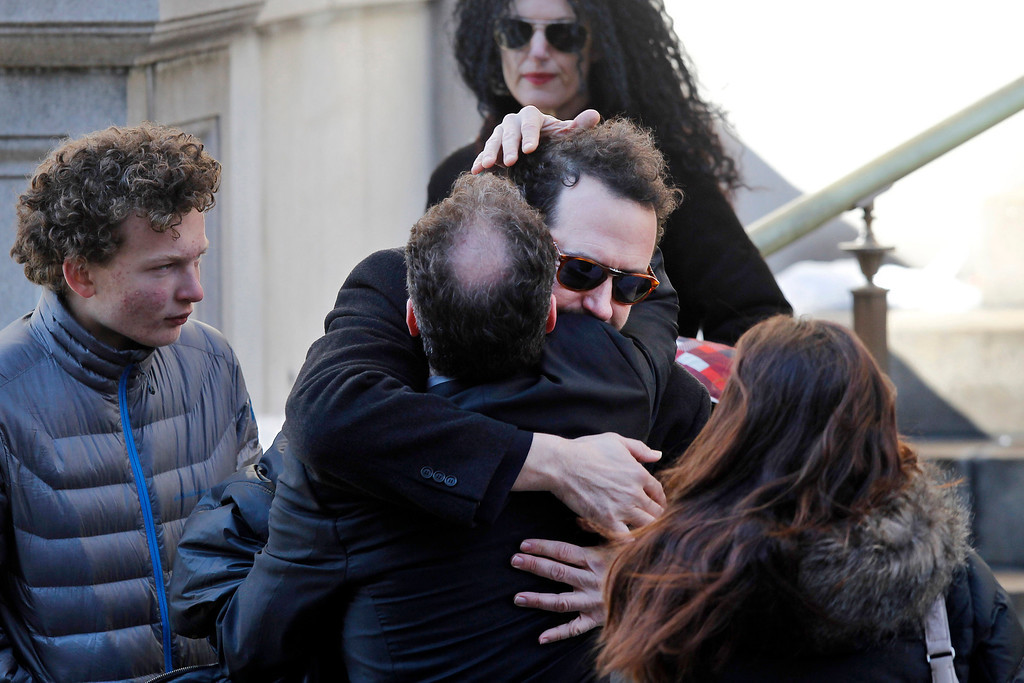 . Writer David Bar Katz is embraced as he arrives at the Church of St. Ignatius Loyola for the private funeral of actor Philip Seymour Hoffman Friday, Feb. 7, 2014, in New York. Hoffman, 46, was found dead Sunday of an apparent heroin overdose. (AP Photo/Jason DeCrow)