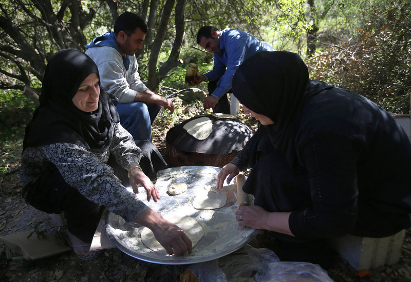 . Syrian refugee women make Syrian flat bread, as they prepare lunch for the United Nations High Commissioner for Refugees, UNHCR, chief Antonio Guterres, during his visit at a small refugee camp, in Ketermaya village southeast of Beirut, Lebanon, Thursday March 14, 2013. The number of registered Syrian refugees jumped 10 percent in just one week to more than 1.1 million, a U.N. aid official said Thursday as France pushed for quickly lifting a European Union ban on arming Syrian rebels. (AP Photo/Hussein Malla)