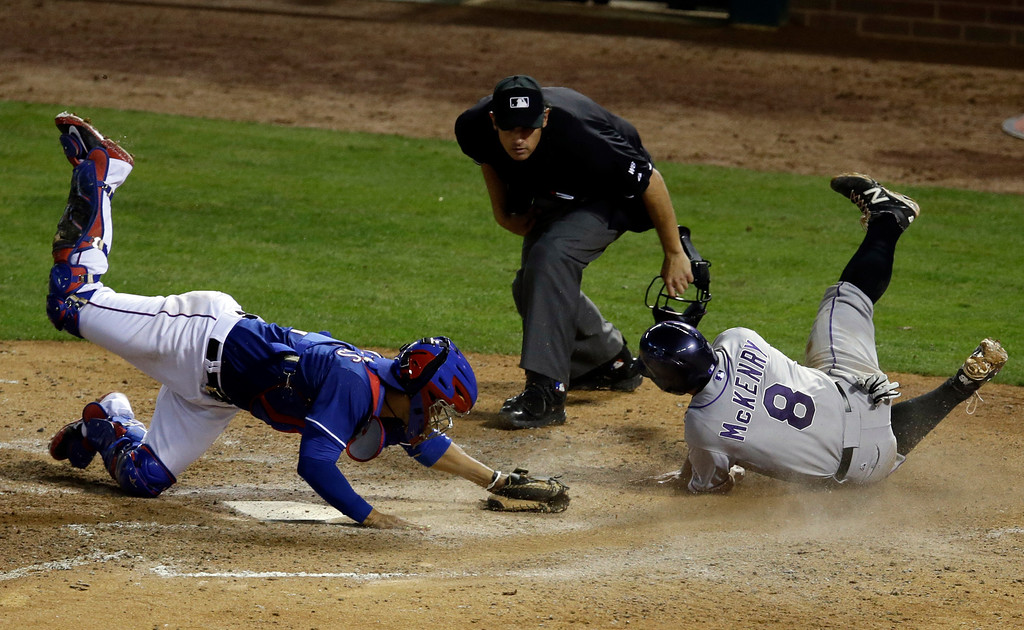 . Home plate umpire Mark Ripperger watches a close play at the plate after Texas Rangers\' Robinson Chirinos (61) tagged out Colorado Rockies\' Michael McKenry (8) who was trying to score from third on a Charlie Blackmon fly out in the seventh inning of a baseball game, Thursday, May 8, 2014, in Arlington, Texas.  The play was upheld after a view at instant replay. The Rangers won 5-0. (AP Photo/Tony Gutierrez)