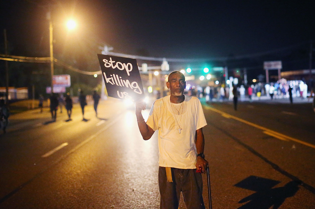 . FERGUSON, MO - AUGUST 18: Frederick Scott protests the killing of teenager Michael Brown on August 18, 2014 in Ferguson, Missouri. Brown was shot and killed by a Ferguson police officer on August 9. Despite the Brown family\'s continued call for peaceful demonstrations, violent protests have erupted nearly every night in Ferguson since his death.  (Photo by Scott Olson/Getty Images)