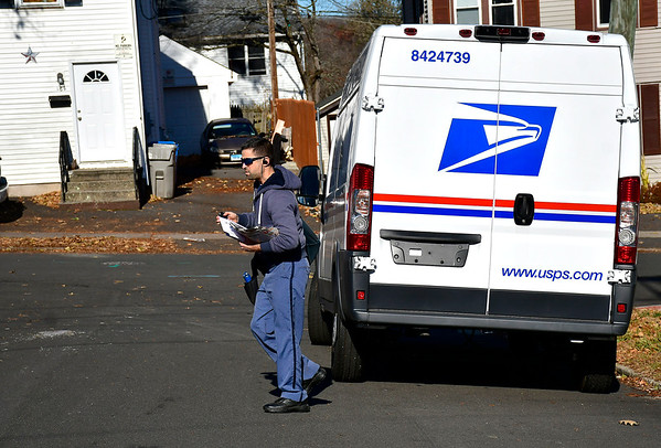 11/23/2019 Mike Orazzi | StaffrBristol postal worker Chris Bachand while collecting food and delivery mail on Edgewood Street in Bristol on Saturday.