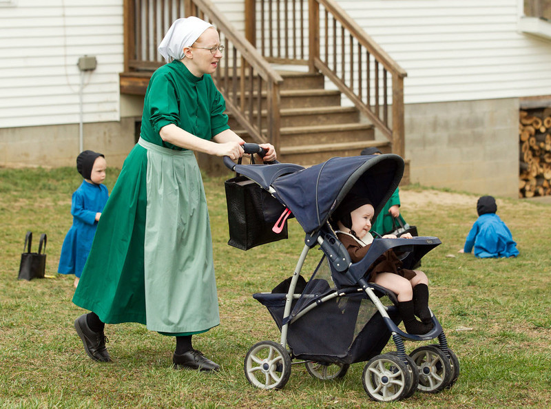 . Emma Miller pushes her son in a stroller outside the schoolhouse in Bergholz, Ohio, Tuesday, April 9, 2013. Miller, along with three other women and a man from this tight-knit community in rural eastern Ohio, will enter prison on Friday, April 12, joining nine already behind bars on hate crimes convictions for hair- and beard-cutting attacks against fellow Amish. (AP Photo/Scott R. Galvin)