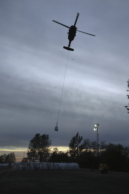 . A helicopter takes off with a bag filled with rock to be dropped on a hole on the lip of the Oroville Dam\'s emergency spillway Monday, Feb. 13, 2017, in Oroville, Calif. The barrier is being repaired after authorities ordered mass evacuations for everyone living below the lake out of concerns the spillway could fail and send a wall of water roaring downstream. (AP Photo/Rich Pedroncelli)