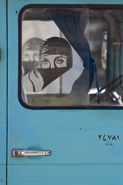 Astara, Iran - February, 2008: Transparent sticker inside a minibus window of a muslim woman covering her face with a headscarf. (Photo by Christopher Herwig)