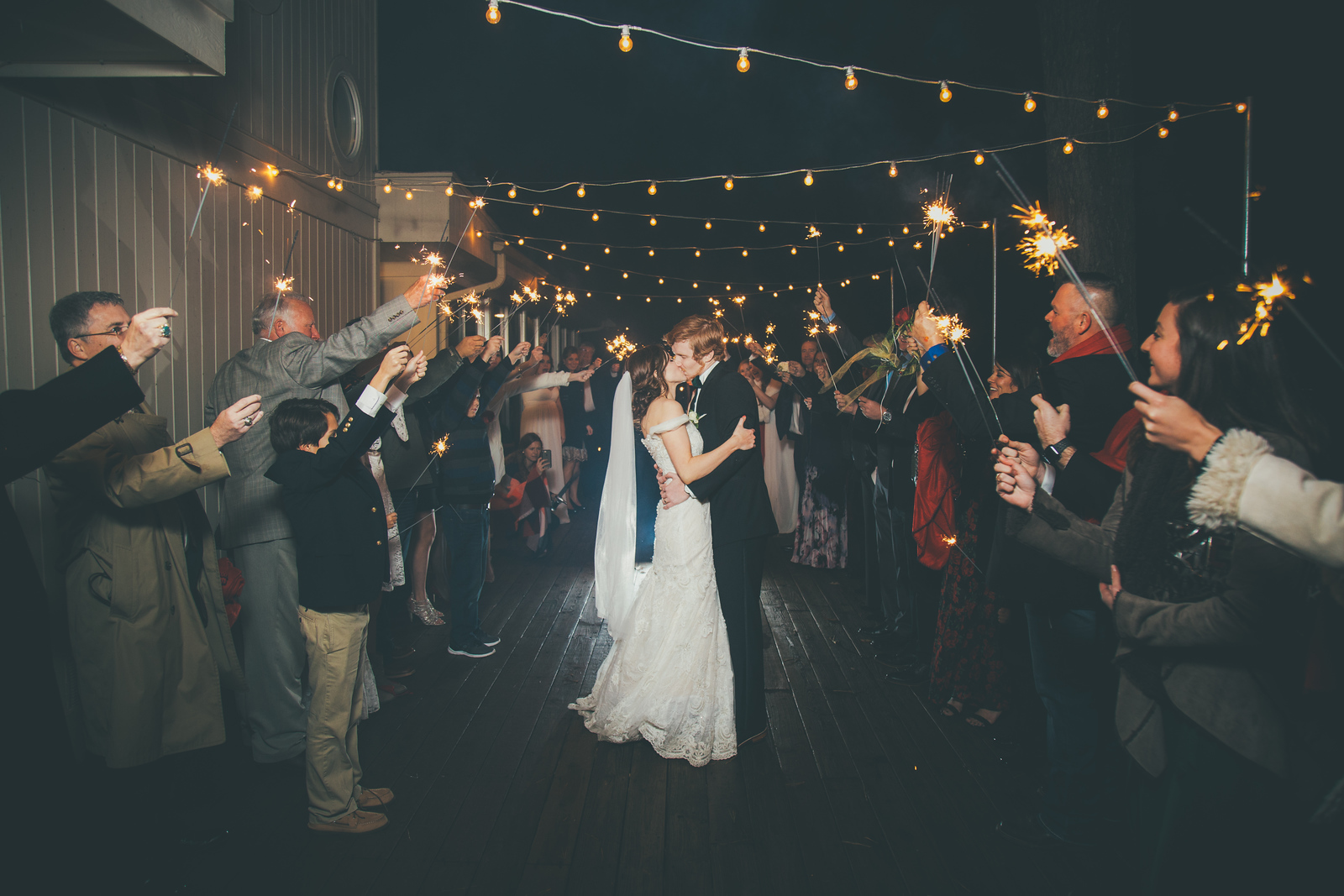 A bride and groom kissing at their grand exit surrounded by guests with sparklers and string lights above