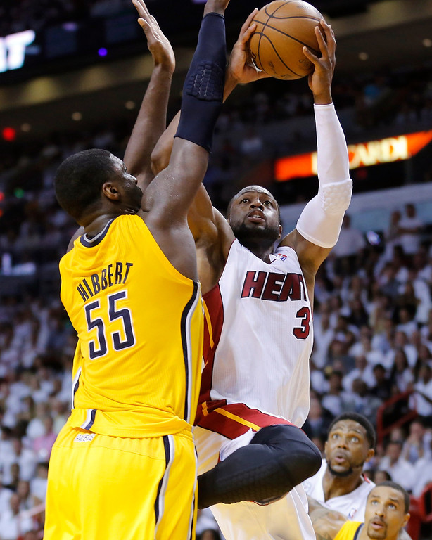 . Miami Heat\'s Dwyane Wade (R) goes up to shoot past Indiana Pacers\' Roy Hibbert during Game 7 of their NBA Eastern Conference final basketball playoff in Miami, Florida June 3, 2013. REUTERS/Joe Skipper